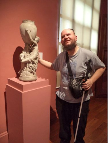 Tony touching a small sculpture of a woman holding a vase.