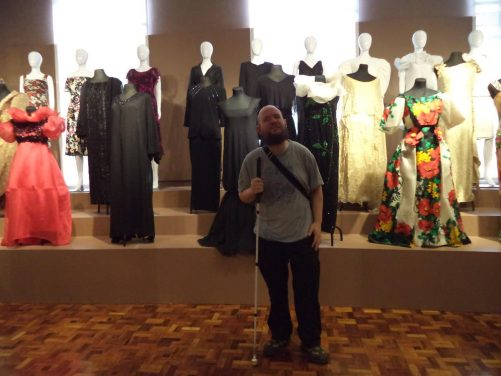Tony in front of a group of female manikins wearing Spanish colonial dresses.