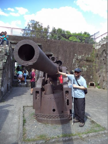 Tony touching a large rusty old Spanish canon near to the walls.