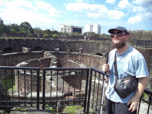 Tony at the fort of Nuestra Señora de Guia within the bastion of Baluarte de San Diego. The fort was built between 1586-1587 and renovated in 1593 to join with the walls of the city. It was destroyed during the Battle of Manila in 1945. The remains of stone walls can be seen in a large circular pit with railings around the edge.