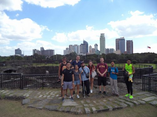 Tony with the group of couchsurfers in front of the ruined fort. Away in the distance are tall modern buildings of the central city.