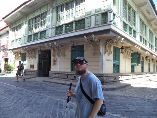 Tony on General Luna outside a Spanish colonial-era building. The first storey and roof overhanging the street and painted in green and cream.