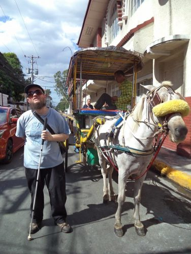 Tony alongside a horse pulling a carriage in Intramuros. The horse-drawn carriage is locally called a Kalesa.