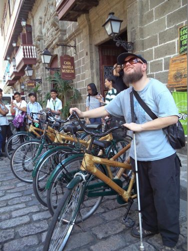 Tony leaning on a bicycle outside Casa Manila Museum. The bicycle is made of bamboo. The museum covers the Spanish colonial era of the Philippines and is housed in a 19th century grand house.