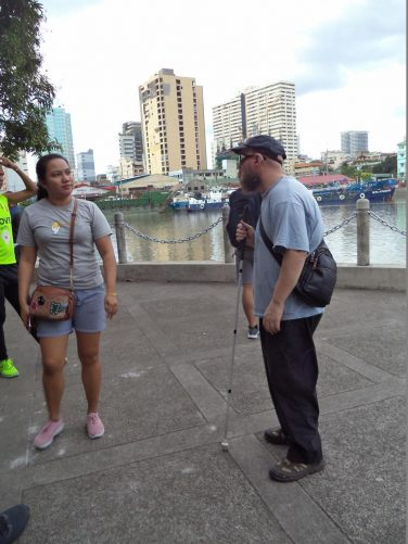 Again Tony next to the Pasig River. Large boats moored on the opposite side and tall office or apartment blocks beyond.