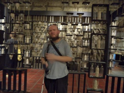 Tony in a room with lots of bottles displayed on shelves. Perhaps some sort of art installation?