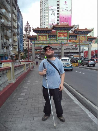 Tony at the north end of Jones Bridge. In front is an arch over the road decorated in Chinese style marking the entrance to Chinatown.