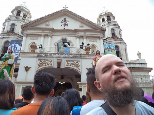 Tony outside the basilica. The front facade in view with a pair of belfries above. There has been a church here since 1586, although construction of the present basilica began in 1933. It was completed in 1984.
