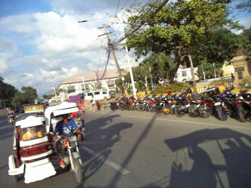 Still travelling on the kalesa, which is passing a public park. A row of motorcycles parked down the side of the road.