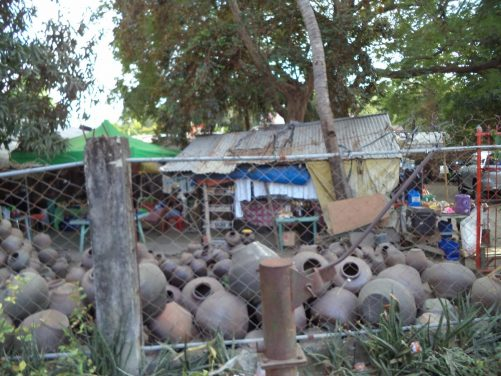 Dozens of large clay pots in a haphazard pile in a compound at the side of the road. These unglazed pottery jars are known as burnay and are produced in the local area. Seen from the kalesa.