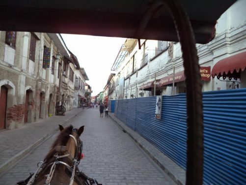 Looking out the front of the kalesa along another part of Calle Crisologo. The cobbled street is lined on both sides with historic colonial-era stone houses.