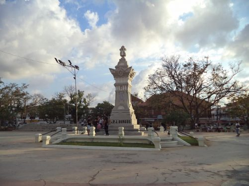View across Plaza Burgos. The square is named after Father José Burgos and a monument to him stands in front. The memorial is in the form of a decorated stone column.