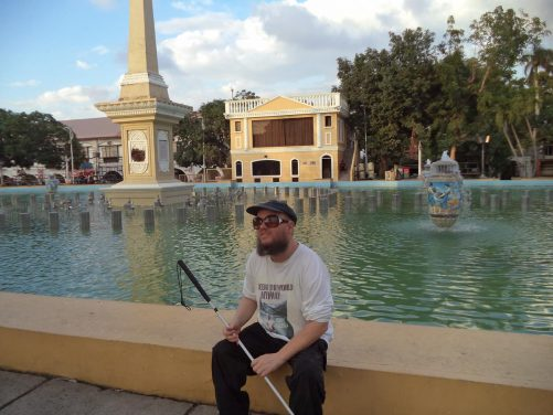 Tony sitting by the pond in Plaza Salcedo. The pond contains a dancing fountain, which is turned on every evening.  Also in view is a stone obelisk, which was part of the plaza's original 17th century design.
