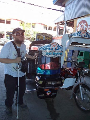 Tony stood next to a colourful pedicab outside Vigan bus station. A pedicab is a 3-passenger motorised public vehicle and useful for short distances. An inexpensive mode of public transport. Found in Filipino towns and cities.