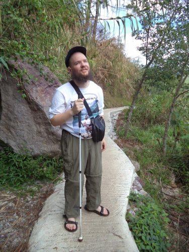 Tony walking down a narrow paved trail towards Bomod-Ok Falls.