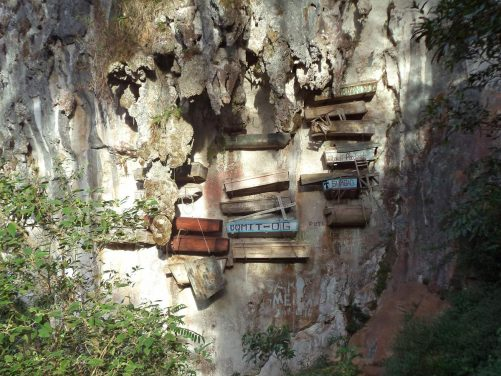 A group of around 17 hanging coffins attached to a cliff face high above the ground in Echo Valley. This is a traditional method of burying people that is still sometimes practised today.