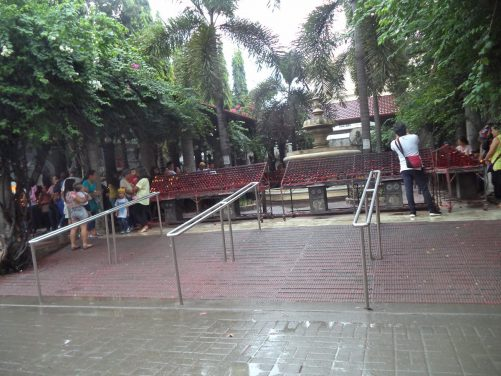 Courtyard within the Minor Basilica of the Holy Child of Cebú, commonly known as the Basilica of Santo Niño. In front are metal stands where visitors can light prayer candles.