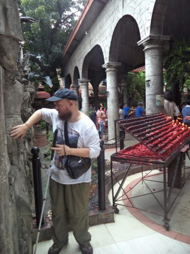 Tony examining another one of the statues. Behind the covered area for lighting prayer candles.