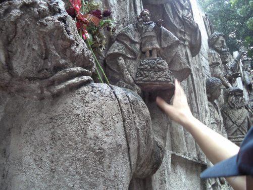 Tony touching a stone copy of the Santo Niño de Cebú statuette.