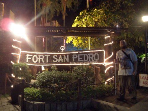 Tony next to an illuminated Fort San Pedro sign.
