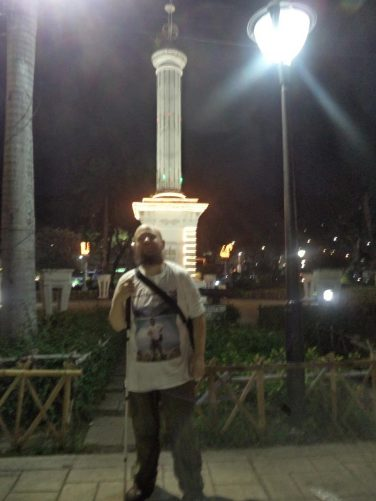 Tony on the edge of Plaza Independencia in semi-darkness. This plaza is located just west of Fort San Pedro. Behind an obelisk dedicated to Miguel Lopez de Legazpi, the first Spanish governor of the Philippines.