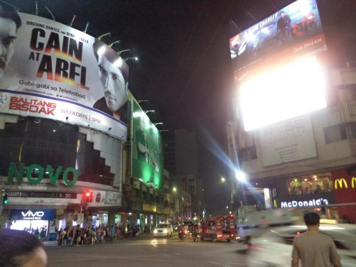 Busy five-way intersection on Colon Street lined with shops and other businesses. Large billboards lit up above.