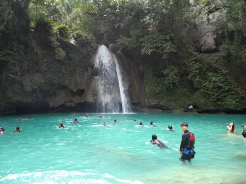 Another view of the falls dropping over a wooded cliff into a large turquoise pool beneath.