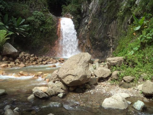 View of Pulangbato 'red rock' Falls. Water crashing over a cliff into a rock and boulder strewn pool. This delightful waterfall is located in the Ocoy Valley in the town of Valencia, Negros Oriental, roughly 20-30 minutes motorbike ride from Dumaguete City.