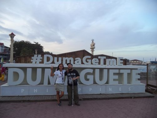 Tony in front of a large 'Dumaguete' sign with a local lady named Leny.