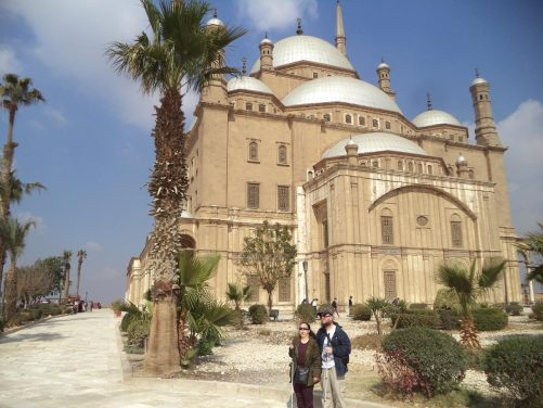 Tatiana and Tony in Cairo Citadel with the exterior of Muhammad Ali Mosque immediately behind. The mosque's thick limestone walls are topped with a central dome which is 21 metres in diameter and 41 metres in height from the ground. The dome is surrounded by smaller domes and half domes. Two elegant cylindrical minarets of Turkish type with two balconies are situated on the western side of the mosque and rise to 82 meters.