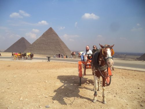 Tatiana and Tony in the horse-drawn carriage. Behind two pyramids can be seen. The nearer one is the Pyramid of Khafre with the Great Pyramid of Giza beyond. The Pyramid of Khafre is the second largest of the Giza pyramids, standing originally at 143.5 metres and now 136 metres. It is 215 metres along its base.
