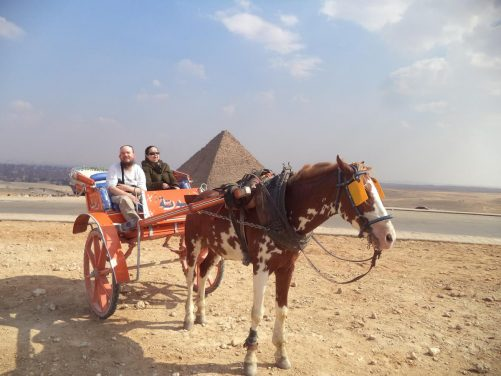 Tony and Tatiana in the carriage with the Pyramid of Menkaure in view. This is the smallest of Giza's three main pyramids at 65 metres in height. Constructed circa 2510 BC during the fourth dynasty, it is thought to have been built to serve as the tomb of Pharaoh Menkaure.