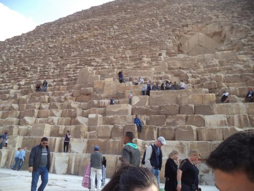 View up one side of the Great Pyramid. People sitting and walking on the lower stones.