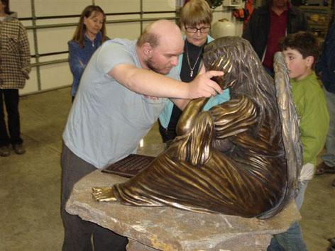 Tony touching angel statue