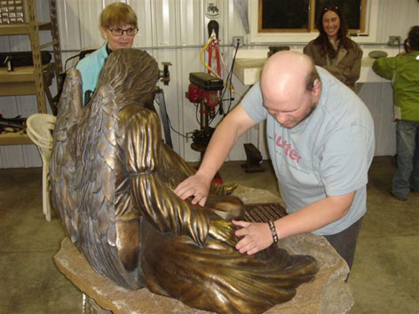 Tony touching angel statue