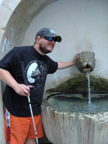 Tony next to a fountain with a lion's head