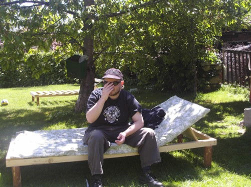 Tony on a sun bed in the guesthouse garden.