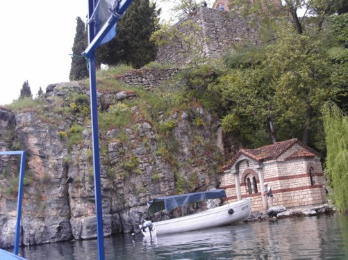 Tiny church of Saint Bogorodica viewed from a boat on Lake Ohrid. The larger 13th century church of Saint John the Theologian (Jovan Kaneo) is just visible on the cliff above.