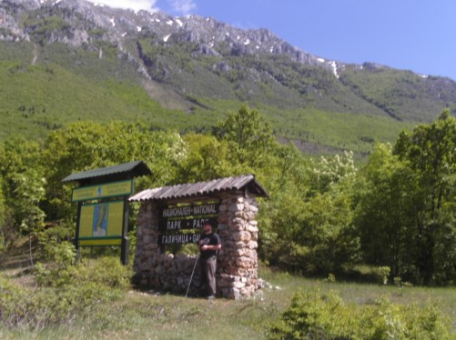 Tony by a sign and information board for the Mount Galicica National Park.