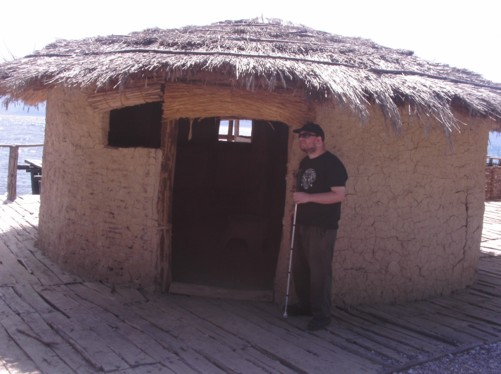 Tony outside a reconstructed prehistoric dwelling made of wood, mud and straw.