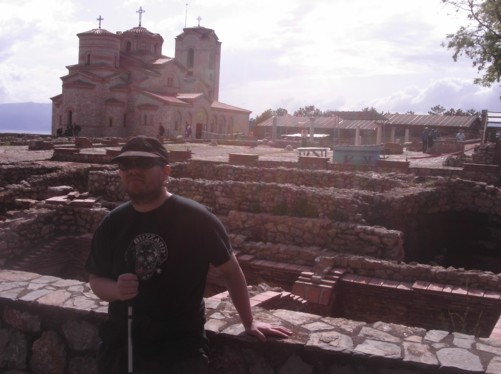 Tony at Plaosnik Archeological site with St. Clement (St. Panteleimon) monastery church behind.