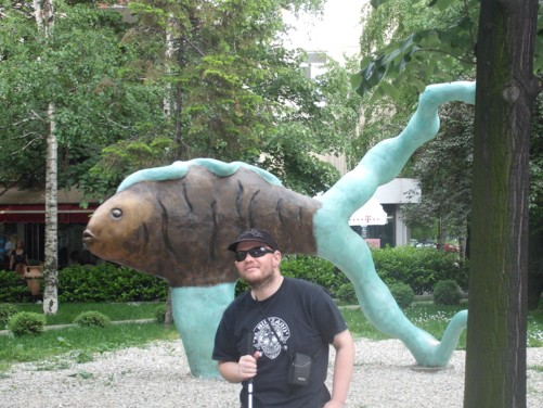 Tony in front of a strange fish statue.