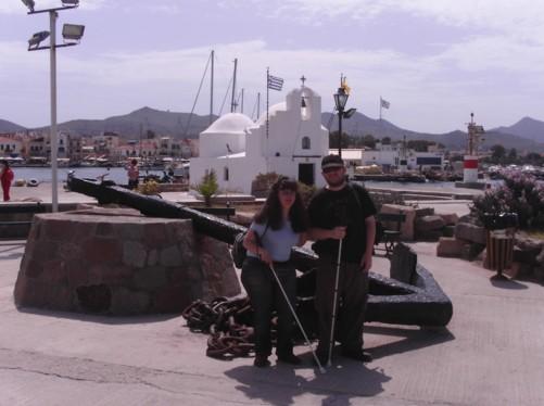 Tatiana and Tony stood by an old ship's anchor, Aegina harbour.