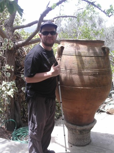 Tony by a large urn at an old style café opposite Athia Temple.