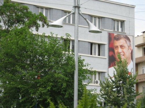 Large poster of Kosovo's Prime Minister Hashim Thaçi on the side of an apartment block.