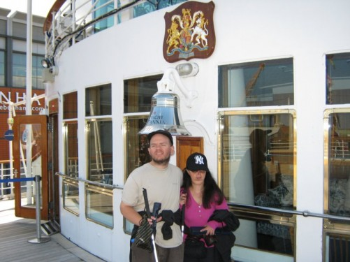 Tony and Tatiana in front of the ship's bell, the Royal Yacht Britannia.