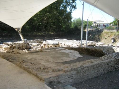 Roman bathhouse ruins under a protective tent.