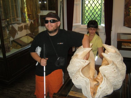 Tony and Tatiana touching a very large clam shell in the monastery museum.