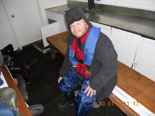 Tony putting on Wellington boots, life jacket and warm clothing in the cabin, preparing to go to Half Moon Island.