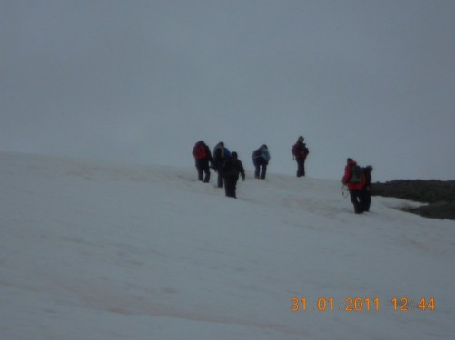 A group of Tony's fellow passengers trekking uphill through the snow.